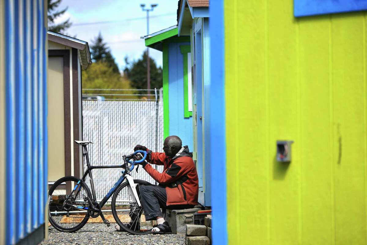Harold Odem works on his bike in front of his tiny house at the Georgetown tiny house village, April 23, 2017.