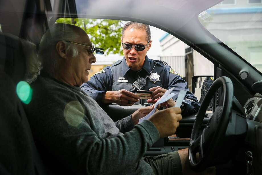 San Rafael police officer Ed Chiu chats with Orlando Guastella (left) after pulling him over. Photo: Gabrielle Lurie, The Chronicle