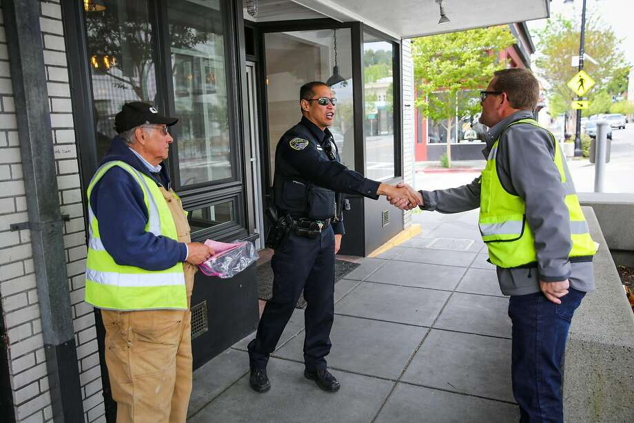 San Rafael police Officer Ed Chiu shakes hands with Chuck Knauer (right) as he engages with the community while on patrol. Photo: Gabrielle Lurie, The Chronicle