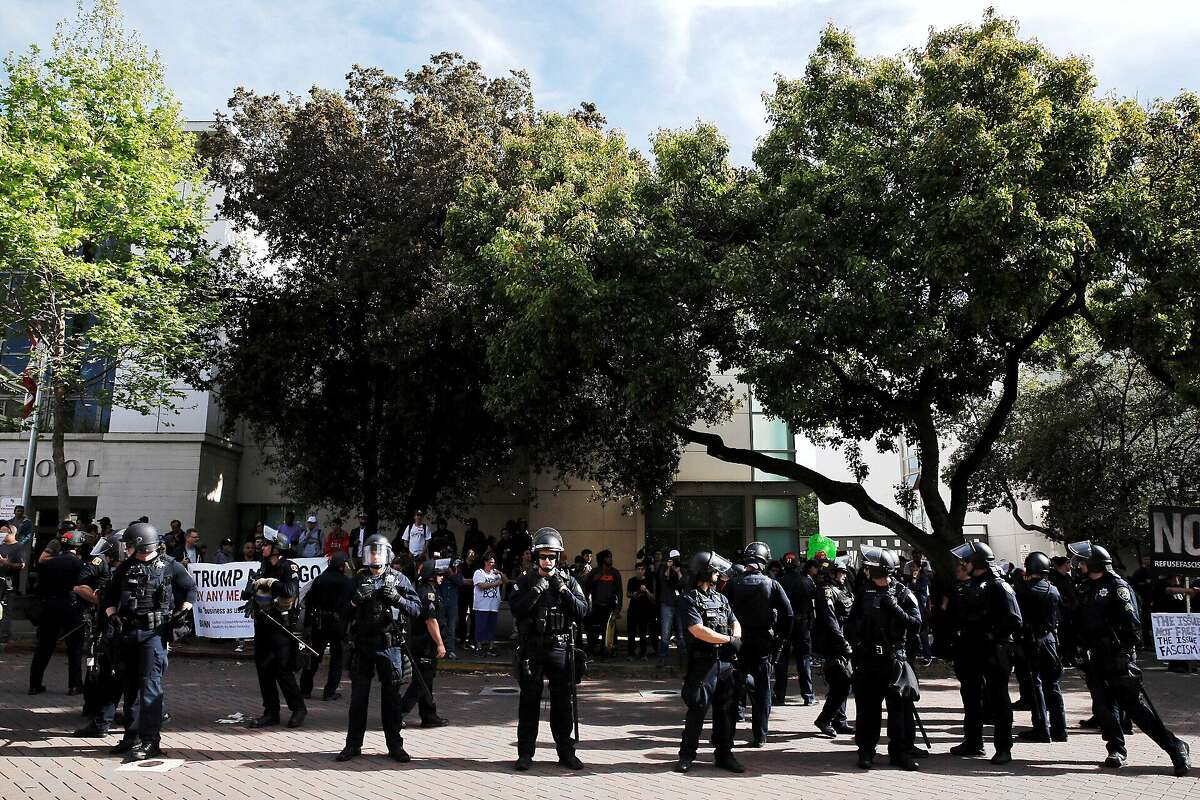 Dozens of police officers divide right wing and left wing demonstrators at MLK Park on Thursday, April 27, 2017, in Berkeley, Calif. Conservative commentator Ann Coulter was to speak at UC Berkeley, but cancelled after groups sponsoring her event no longer supported her appearance.