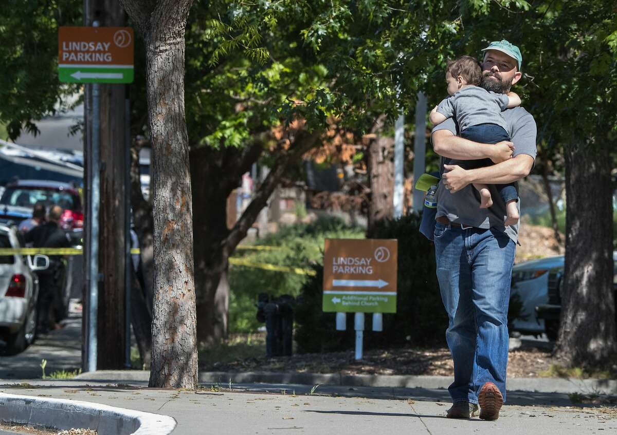 Daniel Robinson, holding son Xavier, walks near where a woman was killed in front of the Lindsay Wildlife Experience museum in Walnut Creek.