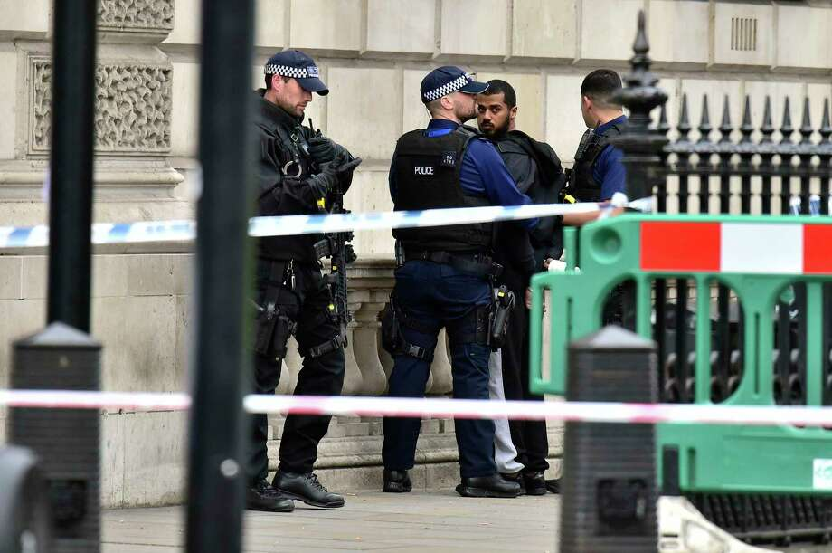 Armed police talk to man at the scene after a person was arrested following an incident in Whitehall in London, Thursday April 27, 2017.  London police arrested a man for possession of weapons Thursday near Britain's Houses of Parliament. (Dominic Lipinski/PA via AP) Photo: Dominic Lipinski, SUB / PA