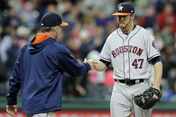 Houston Astros relief pitcher Chris Devenski, right, hands the ball off to manager A.J. Hinch during the seventh inning of the team's baseball game against the Cleveland Indians, Thursday, April 27, 2017, in Cleveland. (AP Photo/Tony Dejak)