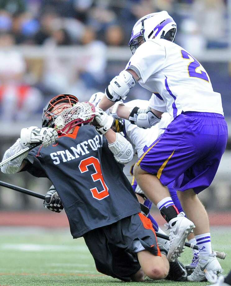 Stamford Dylan Schnieder is checked hard by Dominic Echeverria in a varsity boys lacrosse game at Westhill High School J.Walter Kennedy Stadium in Stamford, Conn. on April 27, 2017. Stamford defeated Westhill 7-6. Photo: Matthew Brown / Hearst Connecticut Media / Stamford Advocate