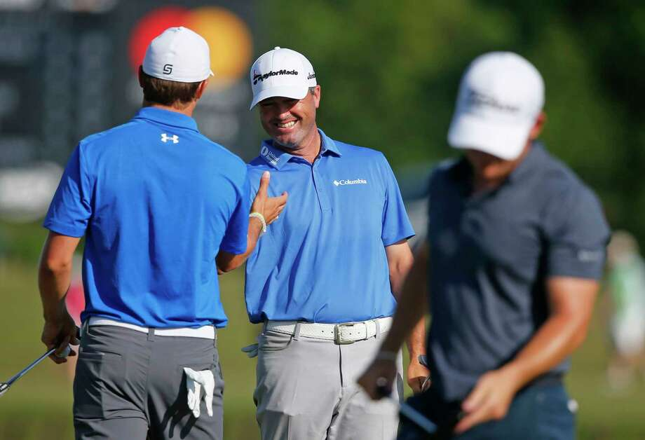 Ryan Palmer, center, smiles after teammate Jordan Spieth, left, sank his putt on the 18th green during the first round of the PGA Zurich Classic golf tournament's new two-man team format at TPC Louisiana in Avondale, La., Thursday, April 27, 2017. They birdied the hole to end the day tied for first at 6 under par. (AP Photo/Gerald Herbert) Photo: Gerald Herbert, STF / Copyright 2017 The Associated Press. All rights reserved.