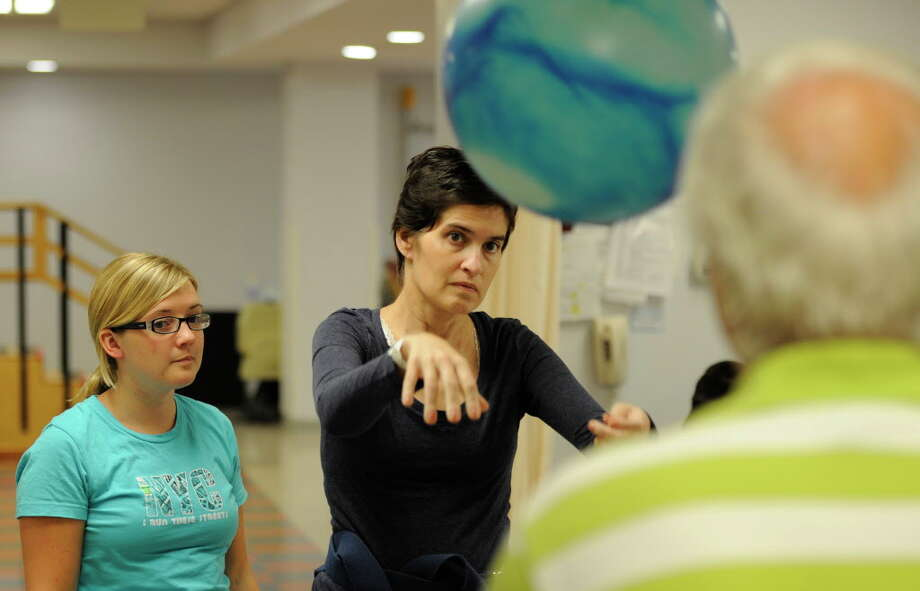 Jennifer Lasher Tinsmon, center is assisted with her physical therapy by Physical Therapist Brigid Kilroy, left and Gary Smith, right at the Sunnyview Rehabilitation Center in Schenectady, N.Y. September 23, 2011.    (Skip Dickstein/Times Union) Photo: Skip Dickstein / 2011