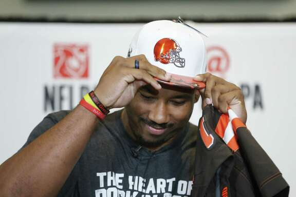 Texas A&M product Myles Garrett puts on a Cleveland hat at a watch part in Arlington. He's the first Aggie to be the first pick.