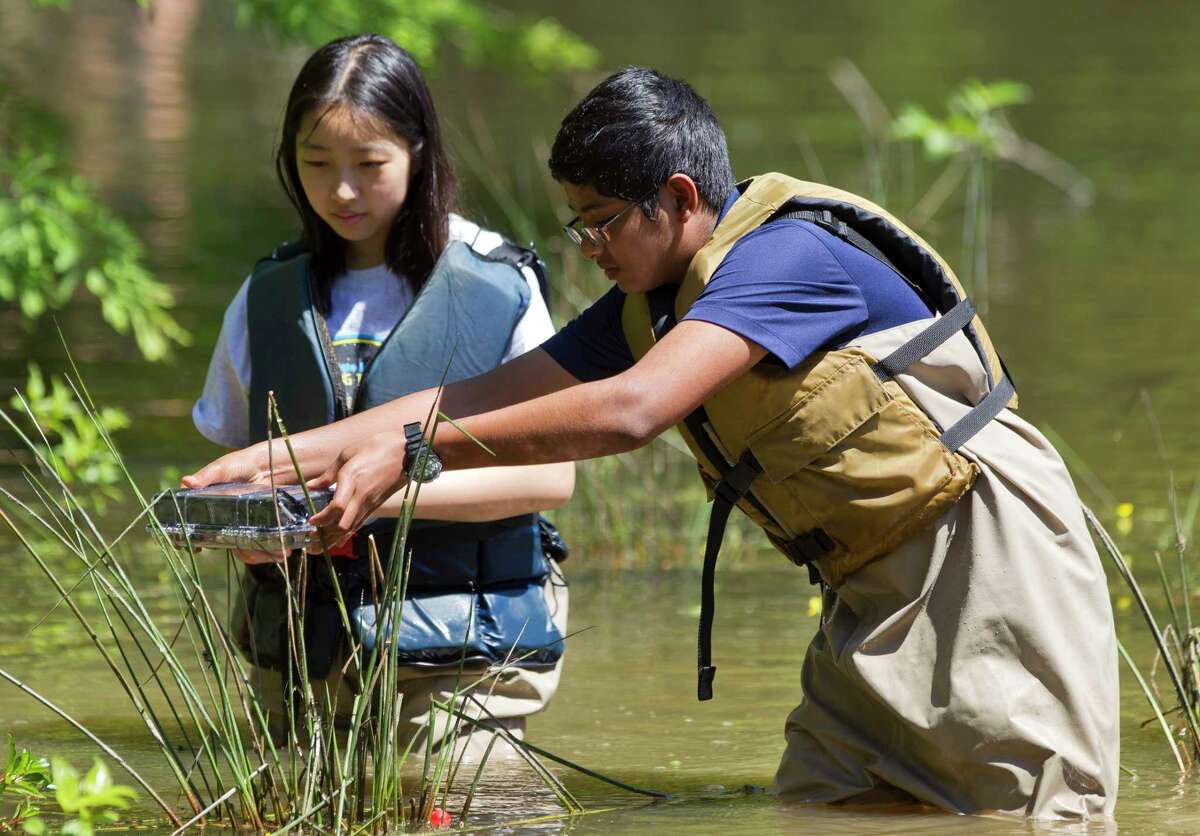 Catherine Zhao, left, and Abhishek Choudhury test lake water as they and other students from the Academy of Science and Technology at The Woodlands College Park High School conducted various environmental experiments at William Goodrich Jones State Forest Thursday.