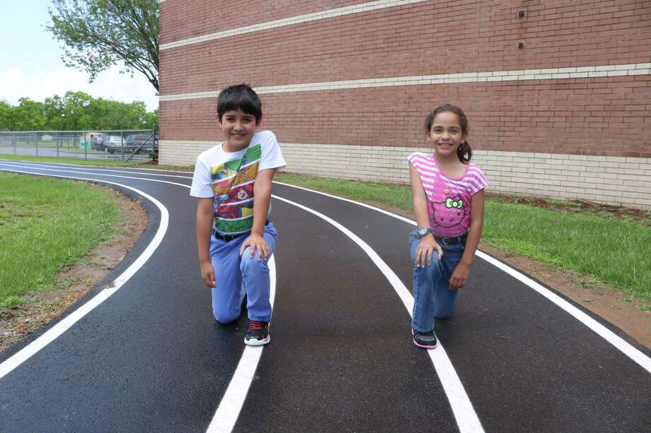 Kneeling on Turner Elementary's brand-new track, third grader Julian Sanchez (left) and fourth grader Athena Velez logged over 200 miles this school year in preparing themselves for Saturday's 39th annual Get Fit Jog. Photo: Robert Avery