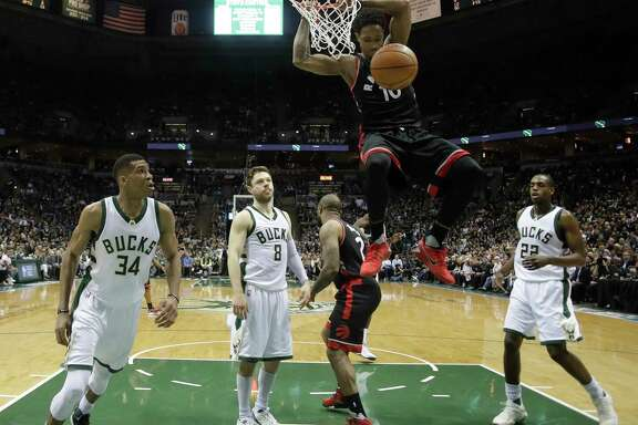 Toronto's DeMar DeRozan puts the finishing touch on a first-half dunk - two of his 32 points in a 92-89 series-clinching victory over Milwaukee.