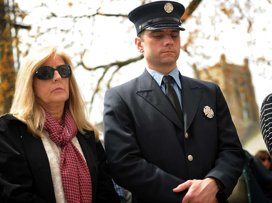 Karen Dumas Ackley, of Fairfield, and her nephew Kevin Dumas, Jr., a Westport firefighter from Milford, observe a moment of silence during the 30th anniversary ceremony of the L'Ambiance Plaza building collapse in Bridgeport on April 24. Dumas Jr.'s uncle, Mario Colello, was the last of the 28 victims pulled from the rubble. Photo: Brian A. Pounds / Hearst Connecticut Media / Connecticut Post
