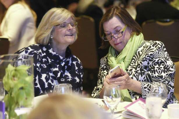 New Canaan residents Catharine Sturgess, left, and Anda Hutchins take part in the Text to Give Campaign, which raised more than $50,000 during the Fairfield County's Community Foundation's Fund for Women & Girls Annual Luncheon at the Hyatt Regency in Greenwich April 20. Women who benefited from the Family Economic Security Program spoke praises and Andrea Jung, the first female CEO at Avon, presented the keynote to a crowd of more than 700.