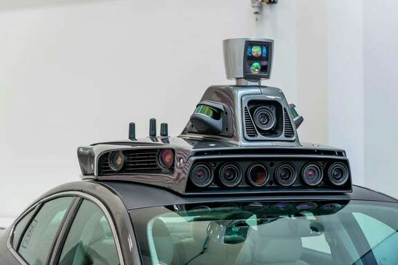 A battery of cameras sits atop a pilot model of an Uber self-driving car at the Uber Advanced Technologies Center in Pittsburgh.