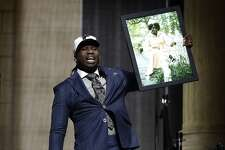 UCLA's Takkarist McKinley carries a photograph of his grandmother onstage after being selected by the Atlanta Falcons during the first round of the 2017 NFL football draft, Thursday, April 27, 2017, in Philadelphia. (AP Photo/Matt Rourke)