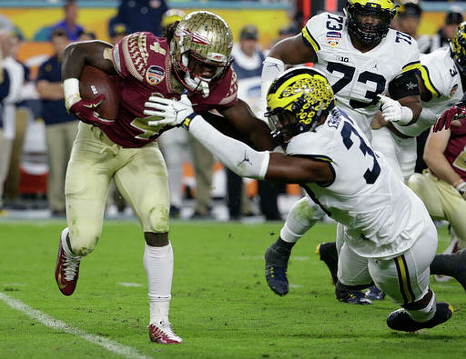 FILE - In this Dec. 30, 2016, file photo, Florida State running back Dalvin Cook (4) runs the ball as Michigan defensive end Taco Charlton (33) attempts to defend during the first half of the Orange Bowl NCAA college football game in Miami Gardens, Fla. After running backs failed to go in the first round of the NFL draft in 2013 and '14, LSU's Leonard Fournette, Stanford's Christian McCaffrey and Cook could be selected on Thursday, April 27, 2017. (AP Photo/Lynne Sladky, File) Photo: Lynne Sladky, Associated Press / Copyright 2017 The Associated Press. All rights reserved.
