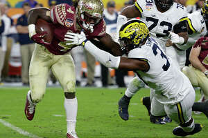 FILE - In this Dec. 30, 2016, file photo, Florida State running back Dalvin Cook (4) runs the ball as Michigan defensive end Taco Charlton (33) attempts to defend during the first half of the Orange Bowl NCAA college football game in Miami Gardens, Fla. After running backs failed to go in the first round of the NFL draft in 2013 and '14, LSU's Leonard Fournette, Stanford's Christian McCaffrey and Cook could be selected on Thursday, April 27, 2017. (AP Photo/Lynne Sladky, File)