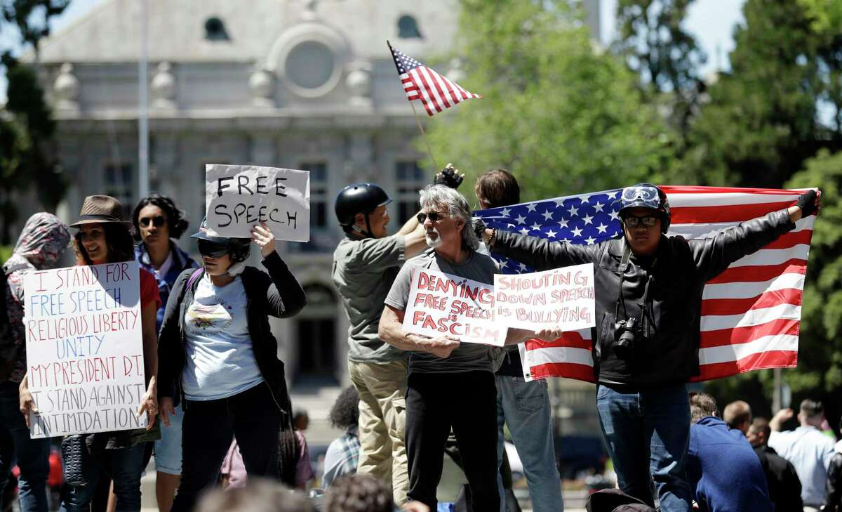 Demonstrators hold signs and flags Thursday, April 27, 2017, in Berkeley, Calif. Demonstrators gathered near the University of California, Berkeley campus amid a strong police presence and rallied to show support for free speech and condemn the views of Ann Coulter and her supporters. (AP Photo/Marcio Jose Sanchez) ORG XMIT: CAMS104