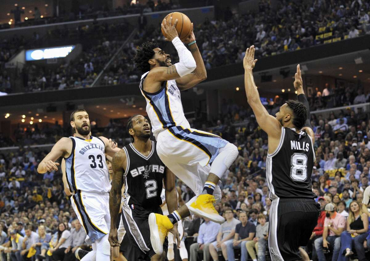 Memphis Grizzlies guard Mike Conley shoots between San Antonio Spurs forward Kawhi Leonard (2) and guard Patty Mills (8) as Grizzlies center Marc Gasol (33) watches during the first half of Game 6 in an NBA basketball first-round playoff series Thursday, April 27, 2017, in Memphis, Tenn. (AP Photo/Brandon Dill)