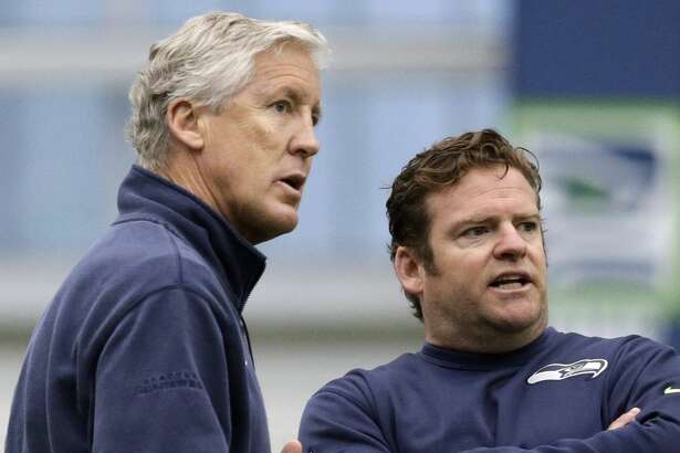 Seattle Seahawks head coach Pete Carroll, left, and general manager John Schneider talk during an NFL football rookie minicamp workout Sunday, May 8, 2016, in Renton, Wash. (AP Photo/Elaine Thompson)