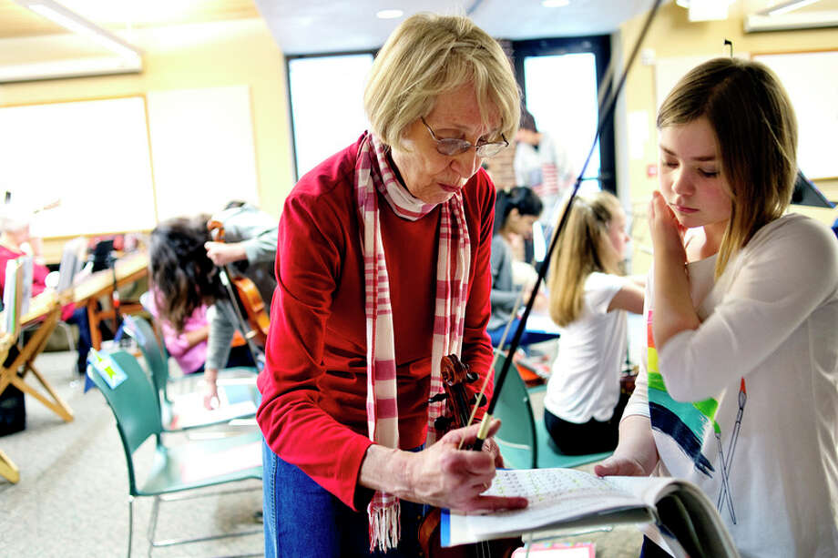 NICK KING | nking@mdn.net  Violin instructor Janet Kroon, left, helps student Amilia Robinette before the Jolly Hammers and Strings Dulcimers concert on Saturday at the Chippewa Nature Center. The concert featured Kroon's students. / Midland Daily News