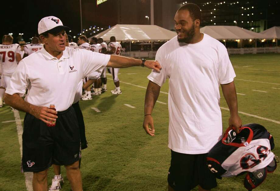 Houston Texans coach Dom Capers greets first-round draft choice Travis Johnson, right, to the team following practice at Houston Texans training facility Saturday, July 30, 2005, at Reliant Park in Houston. Johnson, the 16th overall selection out of Florida State, signed with the team Saturday to complete the Texans draft class. (Photo by Brett Coomer/Houston Chronicle)     HOUCHRON CAPTION (07/31/2005) SECSPTS:  BETTER LATE THAN NEVER:  First-round draft pick Travis Johson, right, is greeted by coach Dom Capes afer ending his one-day holdout. Photo: BRETT COOMER, Houston Chronicle / Houston Chronicle
