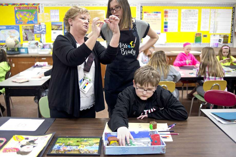 Sixth-grader Benjamin Stebleton, 12, works on his Spongebob-inspired recycling center as paraeducator Mary Priest, left, and art teacher Allison Brady, center, discuss more art supplies for Stebleton's project during art class on Tuesday at Jefferson Middle School. Stebleton is autistic, and he loves Spongebob, drawing and typing. Stebleton drew a picture of Gary the Snail from Spongebob, sent it to Nickelodeon, and the show's cast sent him back an autographed pictured. The picture is his inspiration for the recycling center. Photo: Erin Kirkland/Midland Daily News