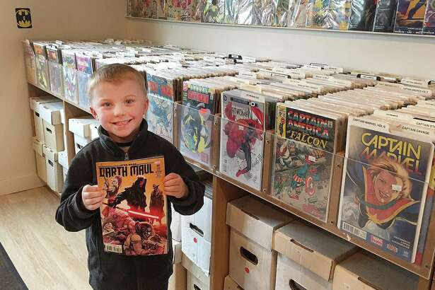 "Ethan McCoy, 6, of Newtown, proudly displays his new Star Wars comic book ""Darth Maul"" after purchasing it at Cave Comics in Newtown, Conn., on Wednesday, April 26, 2017."