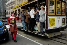 Sir Francis Drake hotel doorman Tom Sweeney greets cable car riders while working on Powell Street in San Francisco, California, on Thursday, April 27, 2017.