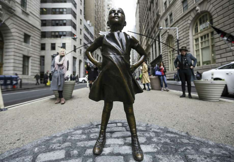 A statue of a defiant girl stands facing the Charging Bull sculpture in the Financial District of New York on March 8, 2017. Photo: Bloomberg Photo By Jeenah Moon. / © 2017 Bloomberg Finance LP