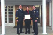 Glen Carbon Police Chief Todd Link, left, honored Hawthorne Animal Hospital for their commitment to provide veterinary service and food, free of charge, to A'to, the K9 Officer with the department. Hawthorne Marketing Director Scott Cates, center, accepted the honor. Also pictured is Glen Carbon Lt. Wayne White.