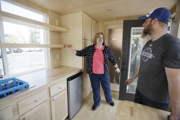 Natalie Woodbury (l to r) talks with Duane Zehm, Escape RV vice president of logistics, as she checks out the shelves in the kitchen in an ESCAPE Vista while touring it on Thursday, April 27, 2017 in San Rafael, Calif.