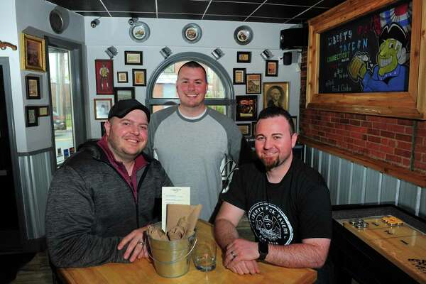 Owners Chris Hey, left, Dan Rizzo, center, and Brian Kearney pose at Liberty Rock Tavern on Bridgeport Avenue in Milford, Conn., on Tuesday Apr. 25, 2017. Not pictured was fellow owner Dan Kardos.