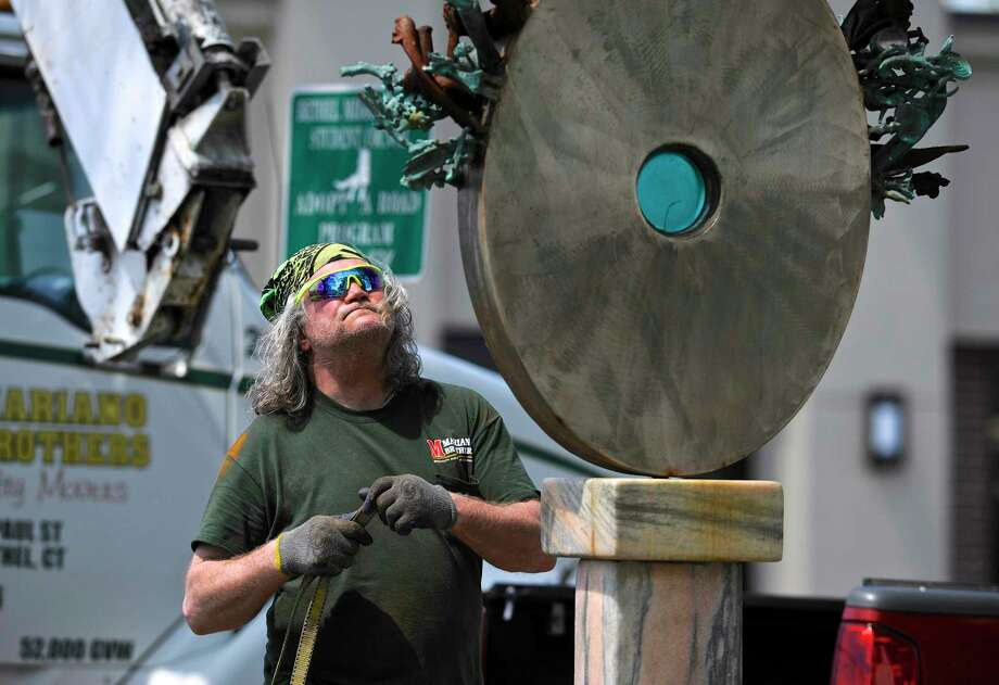 "Don Kane, from Mariano Brothers Specialty Movers, in Bethel, looks over the sculpture, ""Ode To Growth"", by Glenn Zweygardt, that he was removing from it's display location outside of the Bethel Public Library. Sculptures around downtown Bethel, part of the Bethel Arts public sculpture exhibit, were being changed for new pieces. Friday, April 28, 2017, in Bethel, Conn. Photo: H John Voorhees III, Hearst Connecticut Media / The News-Times"