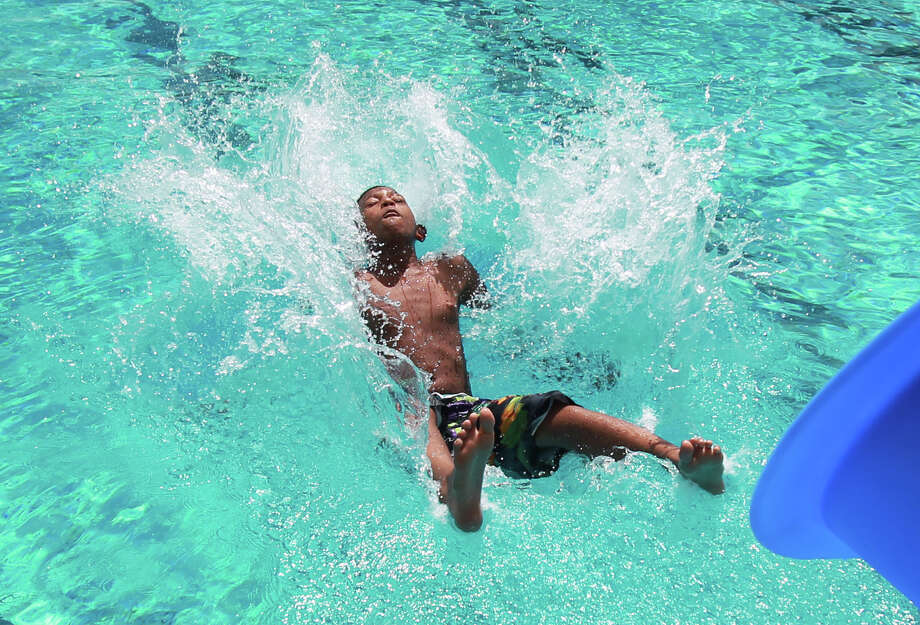 Rashad Coates enjoys the water slide at T.C. Jester Pool. Photo: Mayra Beltran, MBI / Houston Chronicle