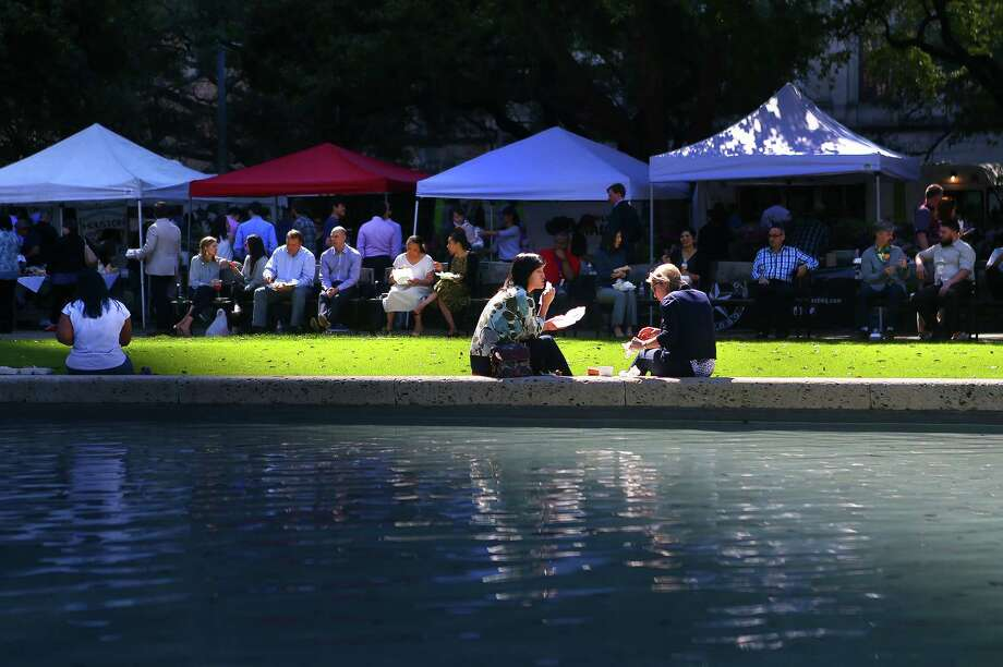People enjoy the City Hall Farmers Market around the reflecting pool at Hermann Square in downtown Houston, Wednesday, Feb. 22, 2017. Back after a winter hiatus, the market runs every Wednesday from 11 a.m. to 1:30 p.m and features local vendors, farmers and food trucks. ( Mark Mulligan / Houston Chronicle ) Photo: Mark Mulligan, Staff / © 2017 Houston Chronicle