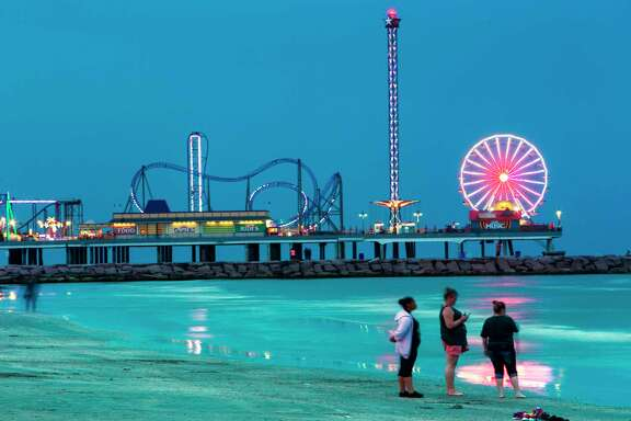 The lights of the Pleasure Pier light up the night sky over the water.
