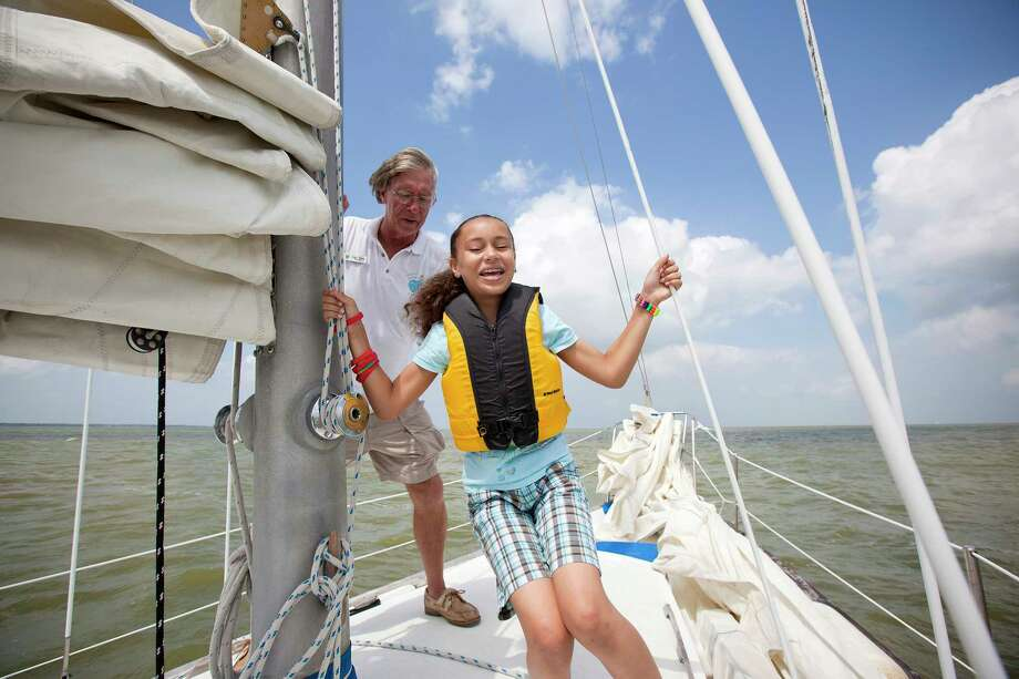 Captain Dave, left, helps 11-year-old Charise Johnson maintain her balance during an educational sailing trip aboard sailing vessel, the Blue Marlin III, Thursday, June 10, 2010 in the waters of Galveston Bay near Kemah, Texas. The trip was lead by Captain Dave McCabe, director of The Heart of Sailing Foundation, an organization that teaches children with special needs how to sail.  (Todd Spoth/Houston Chronicle) Photo: TODD SPOTH, Freelance / Freelance