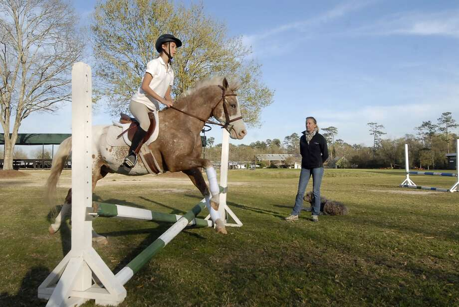 "As Gavi Silverman (14-year-old 8th grader at Awty International School) jumps with ""Toby"" - Merrily Quincoces offers riding lessons at the Houston Polo Club Wednesday 2/27/13. Photo  by Tony Bullard. Photo:  Tony Bullard 2013, Freelance Photographer / © Tony Bullard & the Houston Chronicle"