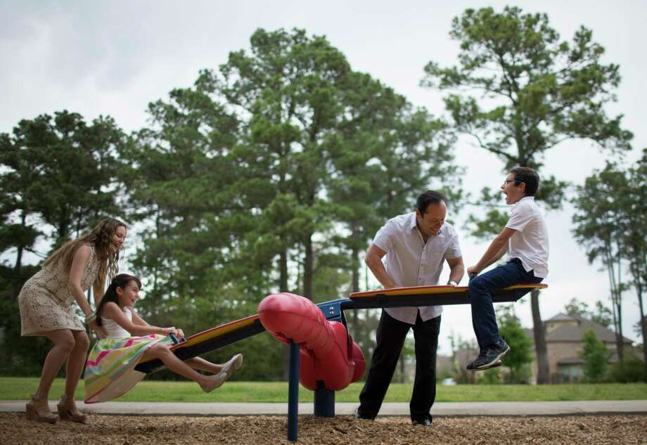 Perla Soto and her husband David Medina enjoy a laugh with their kids Diego Medina, 11, and Paola Medina, 9, as the kids sit on a seesaw at the playground park located right on front of their home in The Woodlands, Saturday, April 1, 2017. The family who relocated from Mexico to The Woodlands seven years ago are planning to move back to Mexico City. ( Marie D. De Jesus / Houston Chronicle ) Photo: Marie D. De Jesus, Staff / © 2017 Houston Chronicle