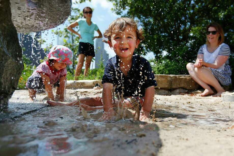 Max Graber, 2, splashes in the watery sand beneath a stone feature at the Fish Family Play Park in Buffalo Bayou Park. Photo: Annie Mulligan, Staff / © 2016 Houston Chronicle