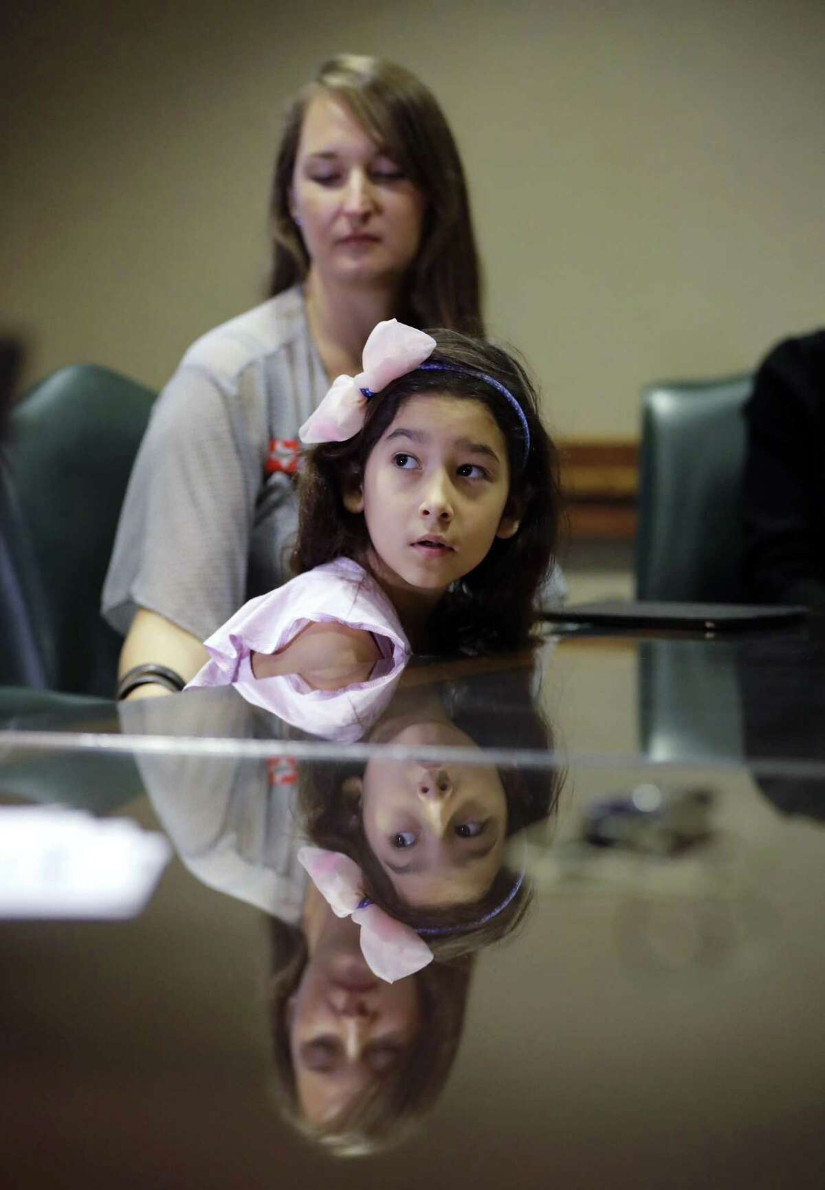 """Libby Gonzales, a transgender girl, sits with her mother Rachel during a news conference held by opponents of a """"bathroom bill"""" at the Texas State Capitol April 19 in Austin. The girl fell asleep before she could testify on a House bill on the matter recently."""