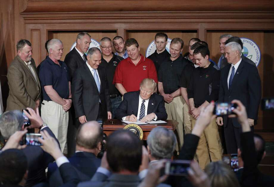 President Donald Trump signs an Energy Independence Executive Order March 28. Such orders are undercutting U.S. leadership in controlling climate change. Photo: Pablo Martinez Monsivais /Associated Press / Copyright 2017 The Associated Press. All rights reserved.