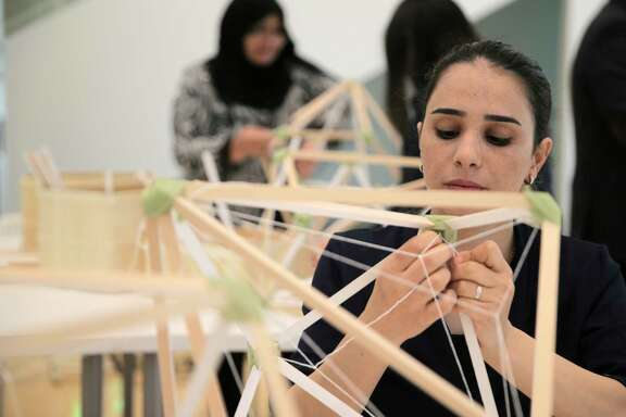 "Samira Houshmand ties string while building lamps for an art installation,  ""Green Light,"" by Danish artist Olafur Eliasson at Rice University's Moody Center."
