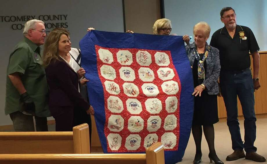Members of the Golden Needles Quilt Guild of Montgomery County show a patrotic quilt it created to help raise funds to move and expand the Montgomery County Veterans War Memorial.