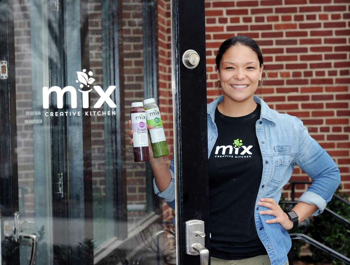 Holidng her restaurant's freshly squeezed juices, Dominique Pustay, marketing director of Mix Creative Kitchen, stnads in the doorway of the newly opened restaurant featuring health food served on-the-go, Greenwich, Conn., Thursday, April 27, 2017.