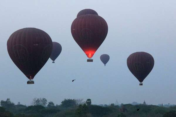 In this Tuesday, March 14, 2017 photo, hot air balloons are seen just after takeoff to fly over the ancient Myanmar city of Bagan. Balloon flights are a popular tourist activity in the city, which is home to the largest concentration of Buddhist temples, stupas and monuments in the world.(AP Photo/Esther Htusan)