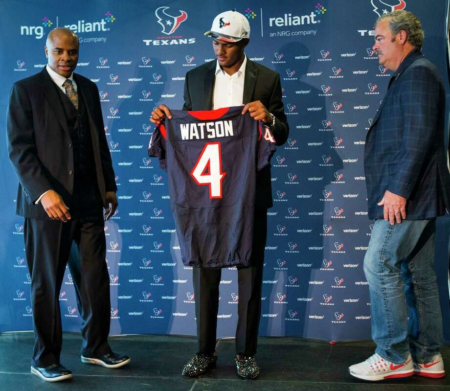 Houston Texans top draft pick Deshaun Watson, center, holds his new Texans jersey as he gets ready to take a photo with general manager Rick Smith and Cal McNair, Texans COO, following a news conference, the day after the Texans made the Clemson quarterback the 12th overall selection in the NFL Draft at NRG Stadium on Friday, April 28, 2017, in Houston. The Texans traded up in the draft with the Cleveland Browns to aquire Watson. Photo: Brett Coomer, Houston Chronicle / © 2017 Houston Chronicle