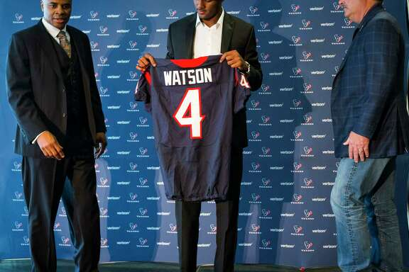 Houston Texans top draft pick Deshaun Watson, center, holds his new Texans jersey as he gets ready to take a photo with general manager Rick Smith and Cal McNair, Texans COO, following a news conference, the day after the Texans made the Clemson quarterback the 12th overall selection in the NFL Draft at NRG Stadium on Friday, April 28, 2017, in Houston. The Texans traded up in the draft with the Cleveland Browns to aquire Watson.