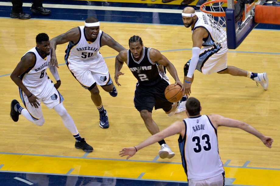 San Antonio Spurs forward Kawhi Leonard (2) drives to the basket between Memphis Grizzlies forward James Ennis (8), forward Zach Randolph (50), guard Vince Carter (15), and center Marc Gasol (33) during the second half of Game 6 in an NBA basketball first-round playoff series Thursday, April 27, 2017, in Memphis, Tenn. The Spurs won 103-96 and advanced to the second round. Photo: Brandon Dill /Associated Press
