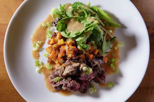 A view of orange marinated grilled hanger stake, with bacon and sweet potato hash with caramelized onions and scallions at the Capital Bistro on Monday, April 24, 2017, in Albany, N.Y.  (Paul Buckowski / Times Union)